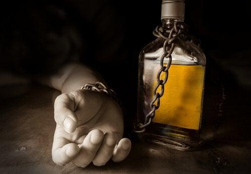 main enchainnée à une bouteille d'alcool